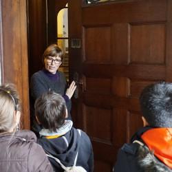 Frau Röhniß öffnet den Kindern eine schwere Holztür