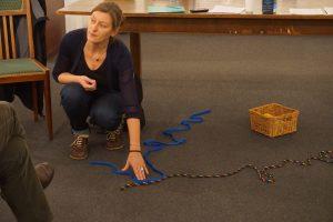 Zwei Seile liegen auf dem Boden. Sie symbolisieren zwei Lebensflüsse. Die Seile liegen wie ein X. An einer Stelle liegen sie etwa zwanzig Centimeter zusammen. Die Referentin weist mit der Hand auf diese Stelle.