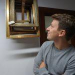 Eine Pate schaut etwas belustigt an eine Sammlung von etwa 8 A4 großen Bilderrahmen, die mit Goldfarbe lakiert sind.