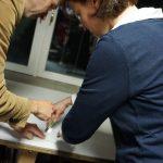 Der Galerist erklärt einer Patin, wie der Glasschneider gehalten werden muss.