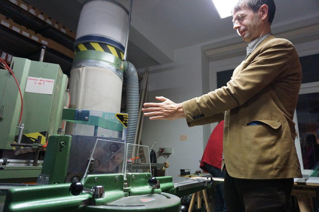 Der Galerist zeigt ein Schneidegerät und zeigt mit seinen Händen den Winkel, mit dem die Leisten beschnitten werden.