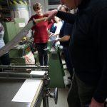 Ein Pate schneidet an einer Hebelschneidemaschiene mit einem etwa ein Meter langem Messer eine weiße Pappe.