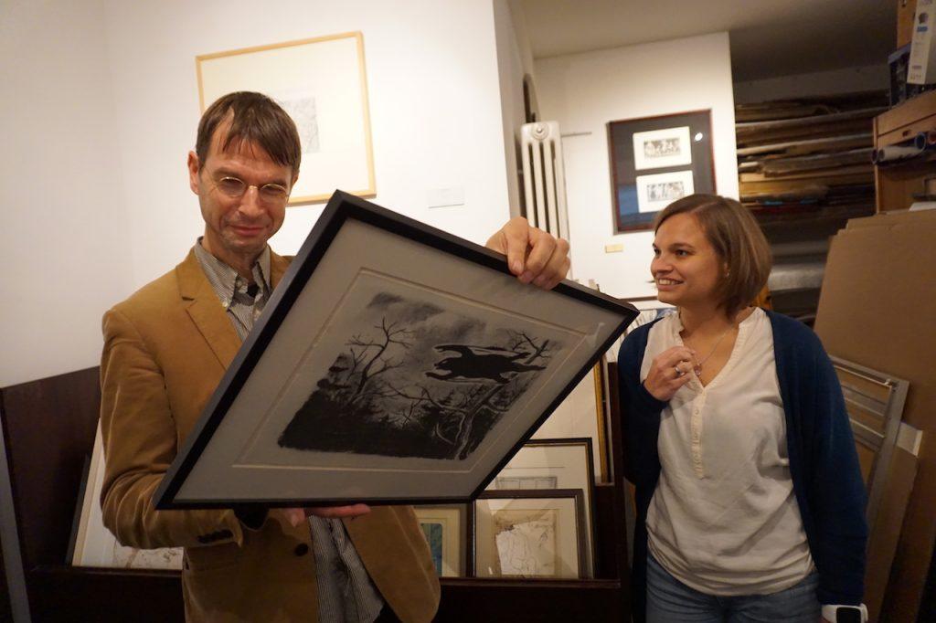 Der Galerist schaut auf die Rückseite eines Bildes, wo der Preis steht. Eine daneben stehende Patin erwartet freudig die Ansage.