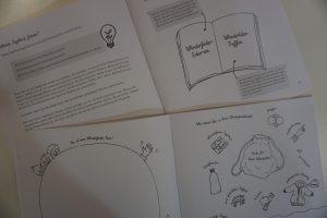 Das Wunderfindertagebuch und das Patenbuch sind aufgeschlagen. beim Patenbuch sieht man die Erklärung zum Aufbau des Tagebuches. Bei dem Wunderfindertagebuch ist eine Seite zum Ausmalen und beschriften aufgeschlagen.