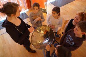 Die Gruppe steht um eine Steel Pan. Die Pädagogin erklärt das Instrument. Die kinder schauen interessiert zu ihr auf.