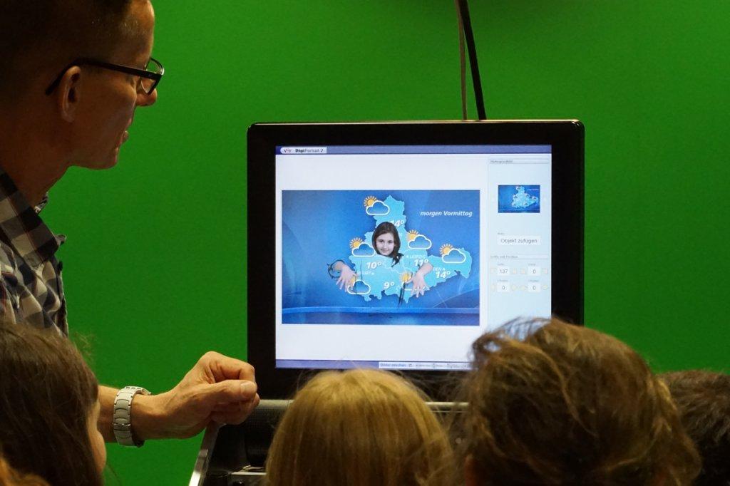 Vor der grünen Leinwand im Greenscreen-Room wird Kindern gezeigt. wie in ein gerade geschossenes Foto eine Wetterkarte von Mitteldeutschlang eingefügt wird. Auf dem Bildschirm sind nur noch der Kopf und die nach vorne ausgestreckten Arme sichtbar.