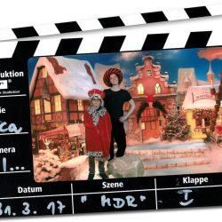 Auf einer Filmklappe ist ein Foto mit mit einem Wunderfinder-Kind und einer Parin, die mit roten Mantel und Hüten verkleidet in einer Winterlandschaft stehen.