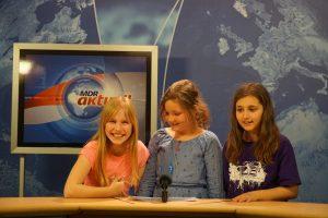 Drei Mädchen stehen vor einer blauen MRD aktuell Wand an einem Tisch mit Mikrophone. Im Hintergrund steht ein Bildschirm mit dem Logo der Sendung.