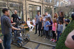 Die Wunderfindergruppe steht neben weiß gekleideten Schauspielern, die auf einer Parkbank sitzen. Vor der Gruppe sind Schienen auf dem Boden, auf denen eine Kamera fährt.